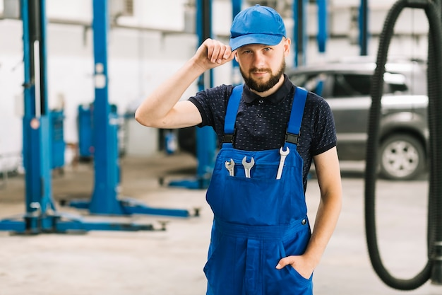 Mechaniker in der kappe an der autowerkstatt