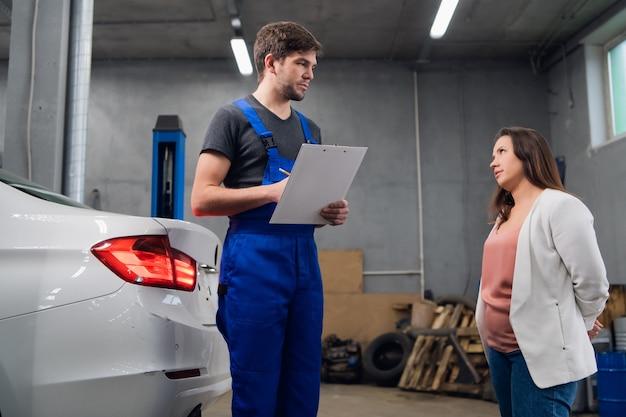 Mechaniker in einem autodienst, der mit einem kunden über eine autoreparatur spricht