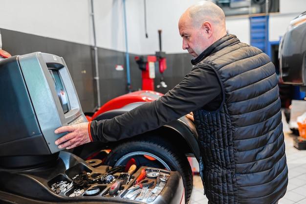 Mechaniker in einer autowerkstatt, der ein rad auf einer ausrichtungsmaschine ausrichtet