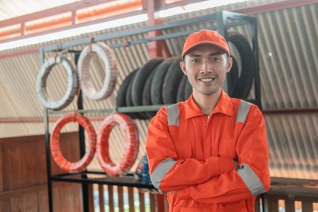 Mechaniker in einer wearpack-uniform mit gekreuzten händen steht mit reifenständer