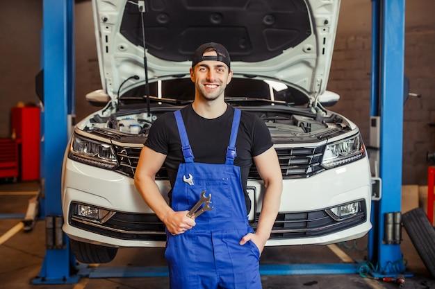 Mechaniker in uniform, der schraubenschlüssel im auto-service-center hält und in die kamera lächelt
