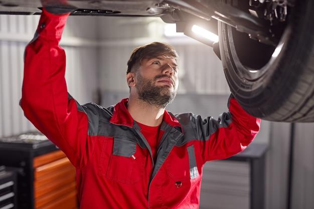 Mechaniker inspiziert fahrgestell eines kaputten fahrzeugs