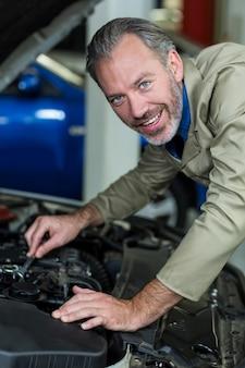 Mechaniker lächelnd, während ein auto motor gewartet