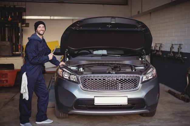 Mechaniker lächelt und hält ein schraubenschlüsselwerkzeug in der garage