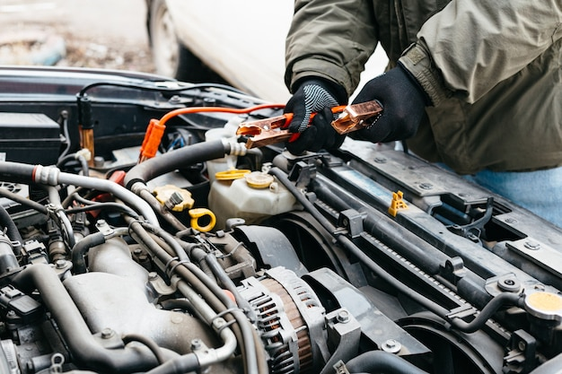 Mechaniker lädt autobatterie mit elektrizität unter verwendung von überbrückungskabeln im freien auf