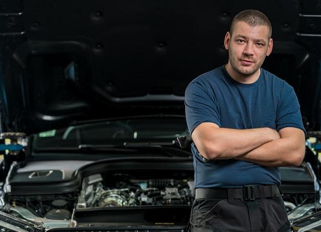 Mechaniker lehnt sich an die motorhaube eines autos