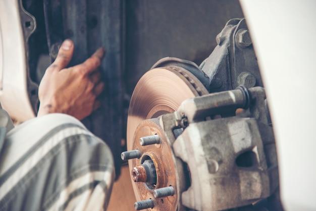 Mechaniker mann autoservice reparatur autoreifen in garage autocar fahrzeuge service