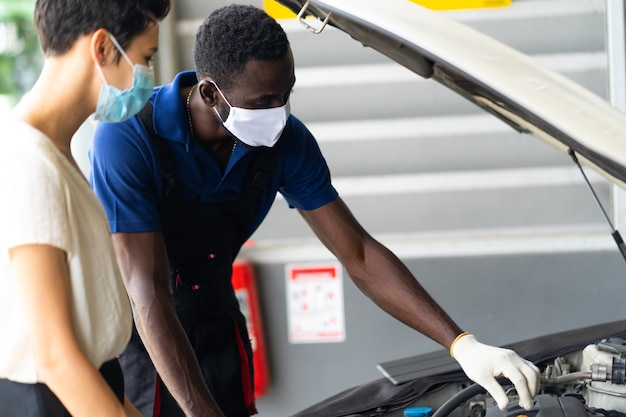 Mechaniker mann und frau kunde tragen medizinische gesichtsmaske schutz coronavirus und überprüfen sie den zustand des autos vor der lieferung.