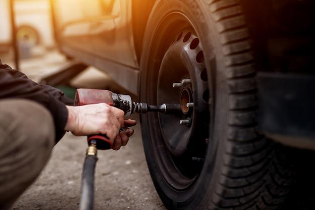 Mechaniker mit einem elektrischen schraubenschlüssel die schrauben vom autorad abnehmen, bevor es abgenommen wird.