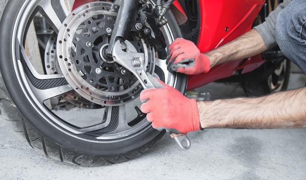 Mechaniker mit einem schraubenschlüssel an einem motorrad. garage. arbeit