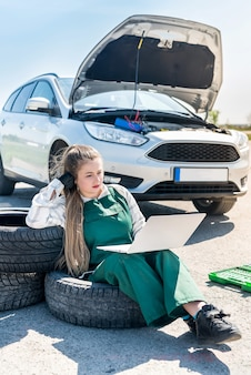 Mechaniker mit laptop diagnostiziert kaputtes auto am straßenrand
