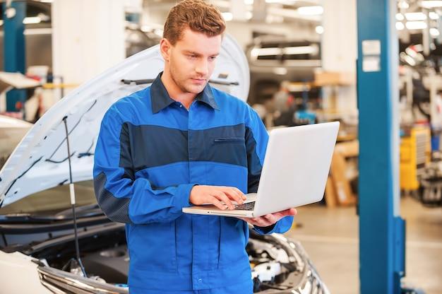 Mechaniker mit laptop. selbstbewusster junger mann, der am laptop arbeitet, während er in der werkstatt mit dem auto im hintergrund steht