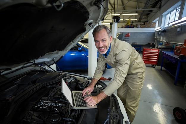 Mechaniker mit laptop, während ein auto motor gewartet