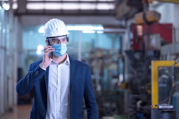Mechaniker mit maske, die am telefon in einer fabrik spricht