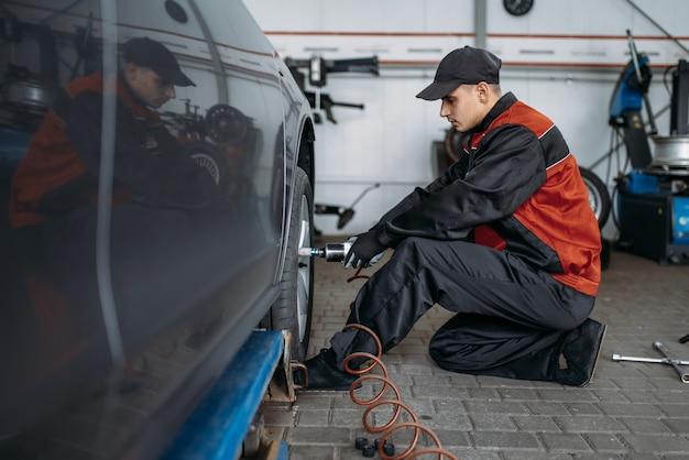Mechaniker mit pneumatischem schraubenschlüssel schraubt das rad im reifenservice ab. mann repariert autoreifen in der garage, autoinspektion in der werkstatt