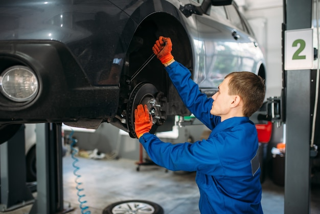 Mechaniker mit schraubenschlüssel repariert die federung des autos
