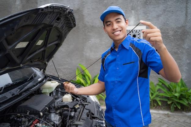 Mechaniker mit uniform inspiziert das autoöl