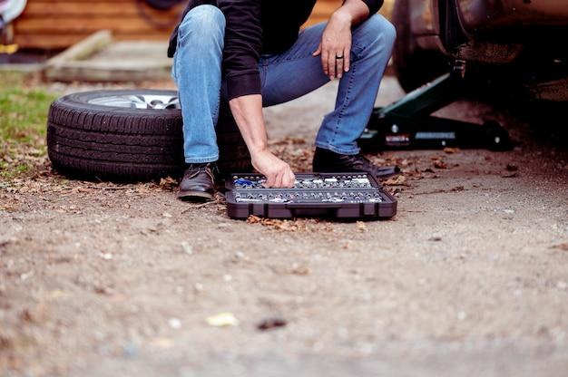 Mechaniker mit werkzeugen, die ein auto reparieren