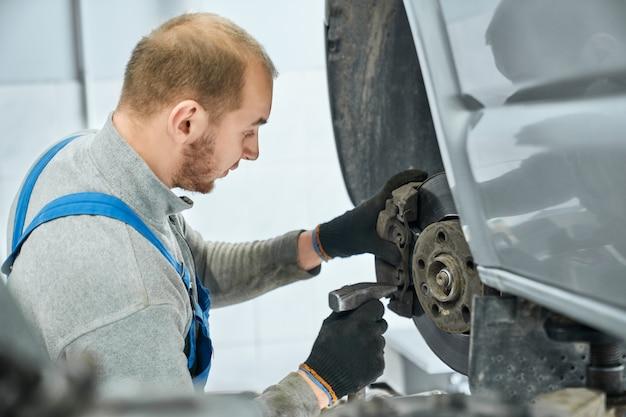 Mechaniker prüft die gebrauchstauglichkeit der bremsbeläge im angehobenen fahrzeug