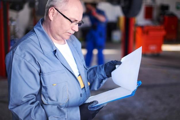 Mechaniker prüft einen fahrzeugbericht