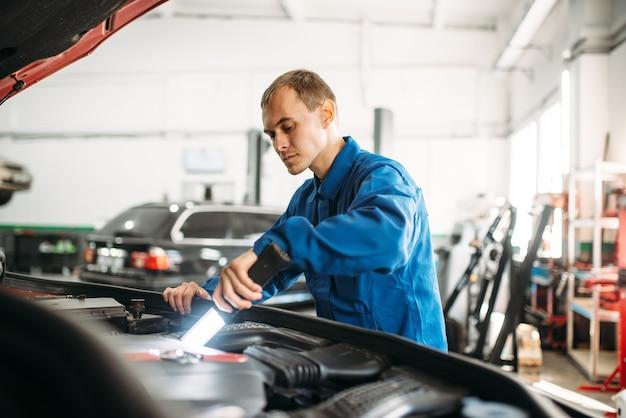 Mechaniker prüft motorraum des fahrzeugs