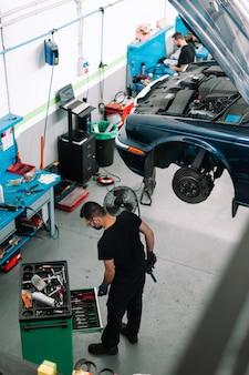 Mechaniker reparieren auto in autowerkstatt