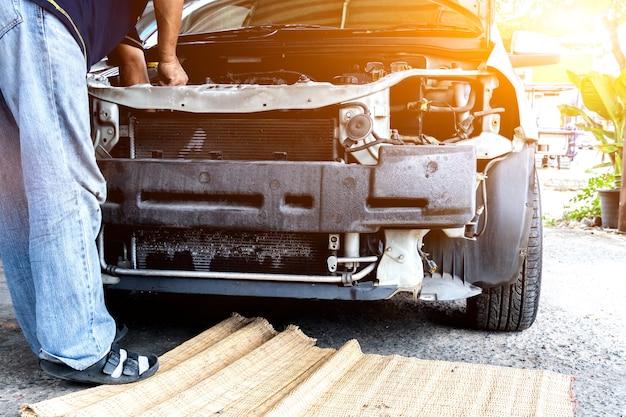Mechaniker repariert auto und wartet fahrzeug in garage. fahr- und transportkonzept.