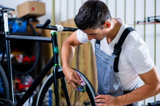 Mechaniker repariert fahrrad in seiner werkstatt
