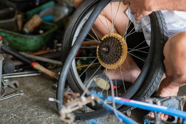 Mechaniker repariert rad des fahrrads, wartung und reinigung