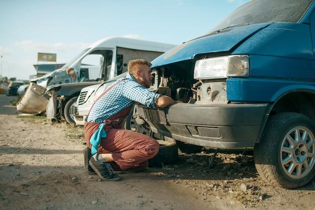 Mechaniker steckte den kopf unter die motorhaube, auto-schrottplatz