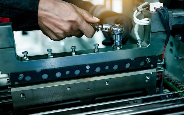 Mechaniker techniker handfixierung industriemaschinen in der fabrik. professionelle techniker-service- und wartungsausrüstung für verpackungsmaschinen. arbeiter verwenden industriemaschinen zur wartung von schraubenschlüsseln.