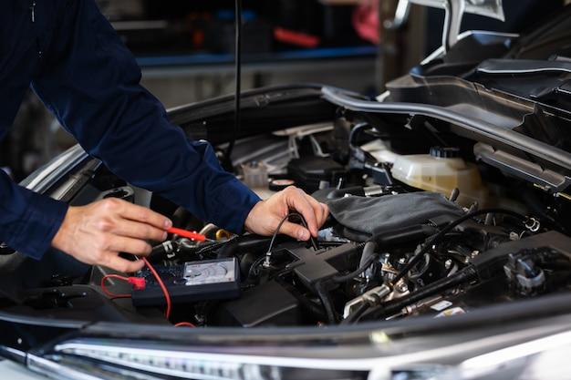 Mechaniker überprüfen die elektrische verkabelung des fahrzeugsystems im autoservice