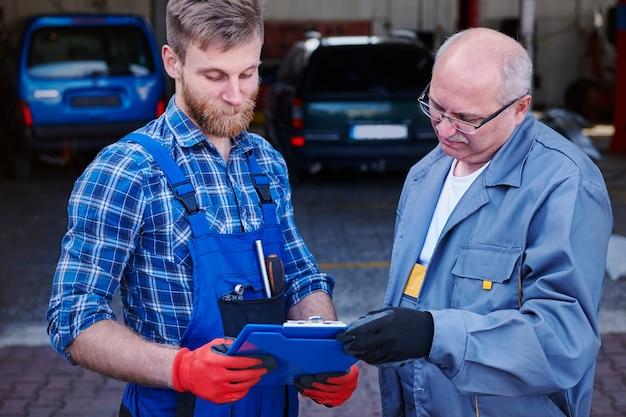 Mechaniker überprüfen eine planung in einer werkstatt