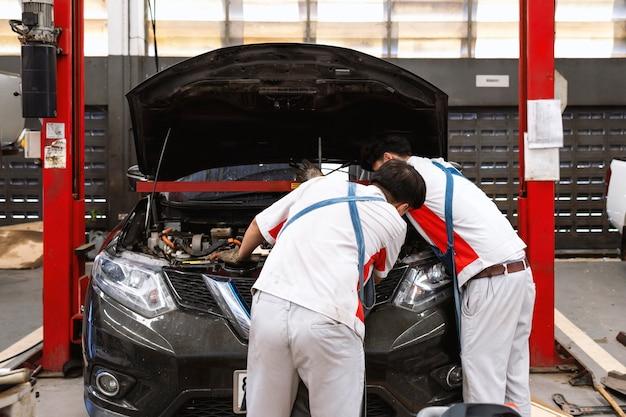 Mechaniker überprüft das auto im kfz-reparatur-service-center