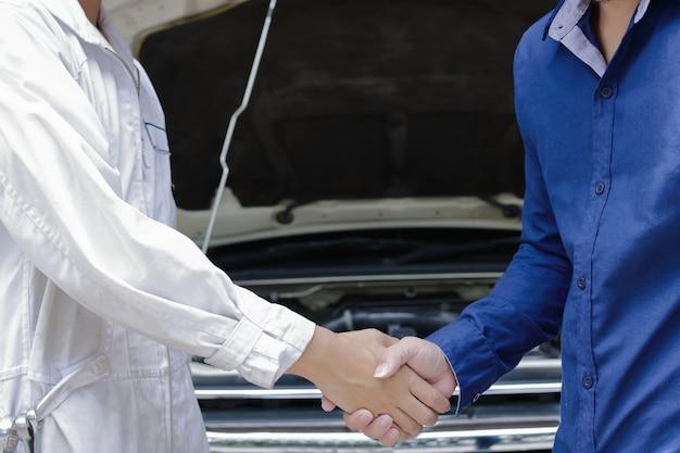 Mechaniker und kunde, die hände nach reparaturmaschine des autos an der selbstbedienungsgarage rütteln.