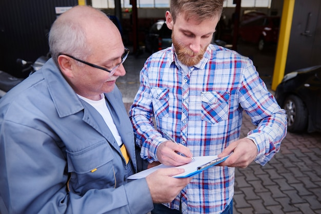 Mechaniker und kunde unterschreiben in der werkstatt ein dokument