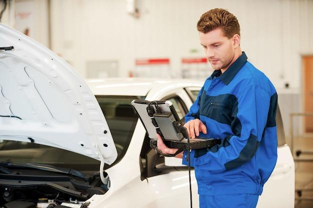 Mechaniker untersucht auto. selbstbewusster junger mann, der an einem speziellen laptop arbeitet, während er in der werkstatt in der nähe eines autos steht