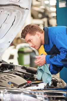 Mechaniker untersucht auto. selbstbewusster junger mann in uniform, der auto untersucht und sich die hände mit lappen abwischt, während er in der werkstatt steht