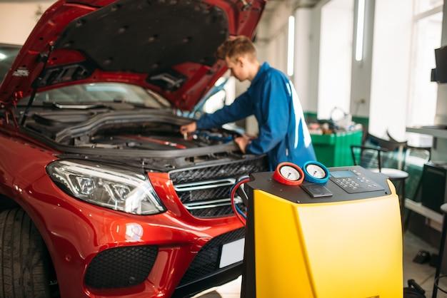 Mechaniker verbindet klimaanlage zur diagnose von freon.