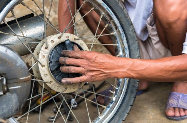 Mechaniker wechselnden motorradreifen nach traditioneller methode