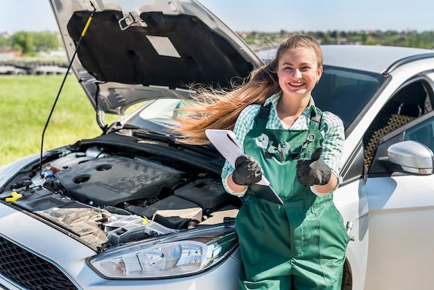 Mechaniker zeigt daumen oben in der nähe des autos mit offener motorhaube