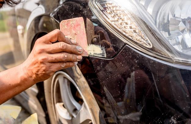 Mechanikerarbeitskraft-schlosserbefestigung zerkratzt auf fahrzeugkarosserie und vorbereiten für das malen.