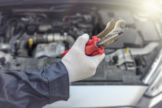 Mechanikerhand mit schraubenzieher reparieren oder auto in garage überprüfen. kfz-service