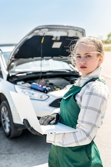 Mechanikerin, die mit laptop vor gebrochenem auto aufwirft
