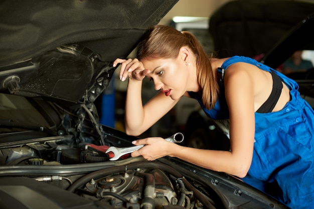 Mechanikerin eines brünetten mädchens, die ein auto repariert oder inspiziert und einen schraubenschlüssel in der hand hält.