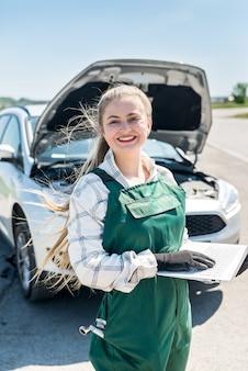 Mechanikerin posiert mit laptop vor kaputtem auto