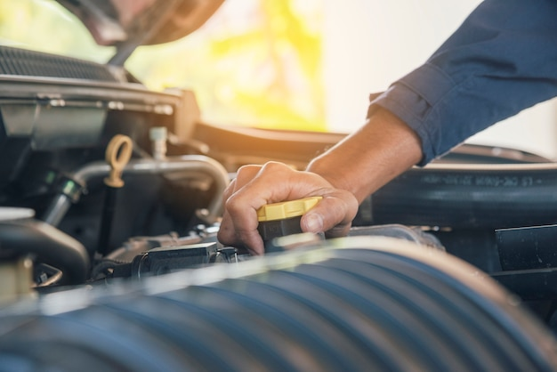 Mechanikermannhände, die auto im automobilautomobilzentrum fixieren.