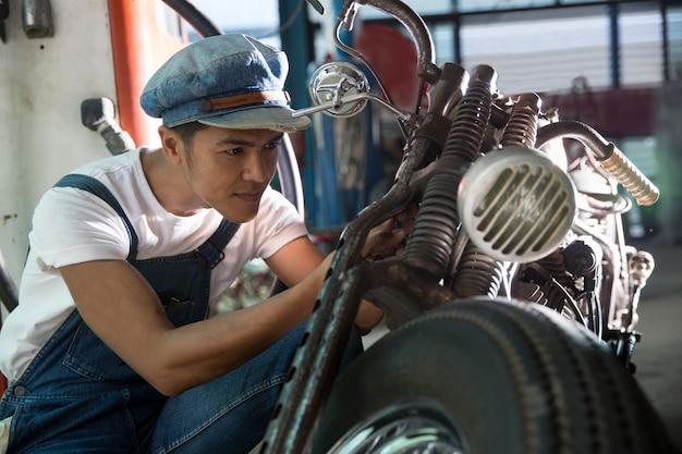 Mechanikerreparaturmotorrad an der werkstatt