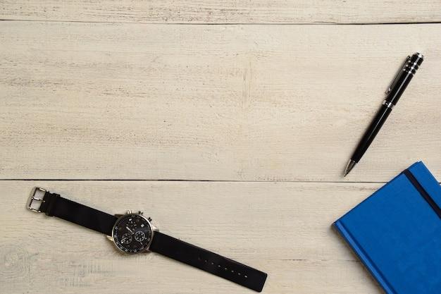 Mechanische armbanduhr, tagebuch und stift liegen auf einem hölzernen leuchttisch