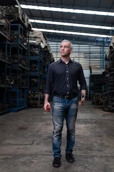 Mechanischer mann besitzer kleinunternehmen, das alte autoteile auf laptop-computer inspiziert, während es in einem großen lager für alte autoteile arbeitet